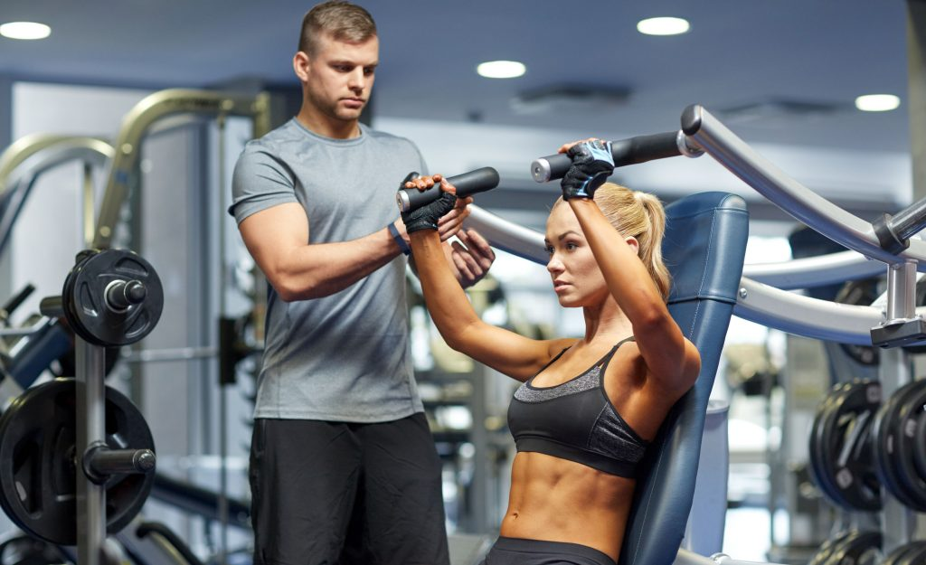A personal trainer helping a woman strength train exercise