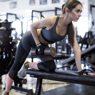 A woman in active wear with a dumbbell.